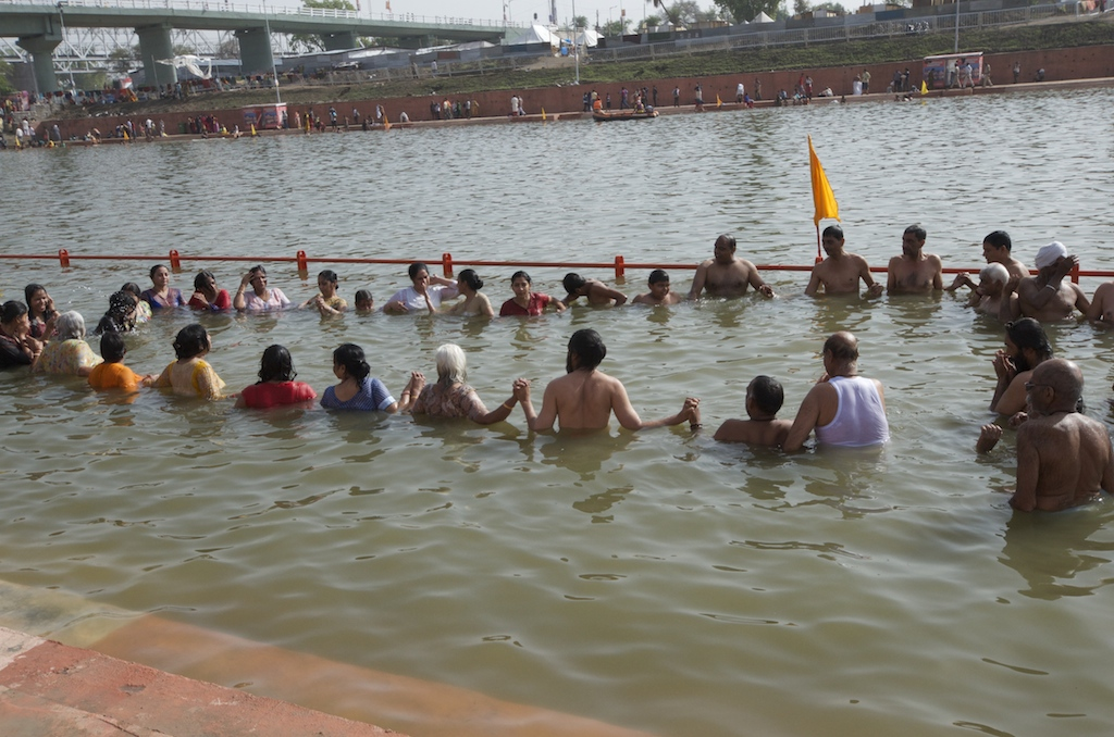 Swamiji leads devotees into the Holy Dip
